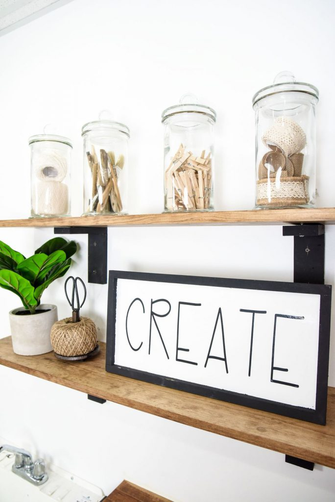 open shelving holding jars, a sign, and made with wooden shelf brackets