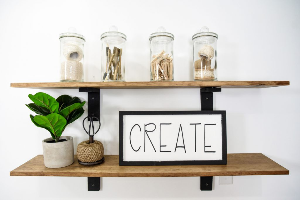 Shelves containing jars of craft supplies, a plant, ball of twine holding scissors, and a wooden frame containing the word Create