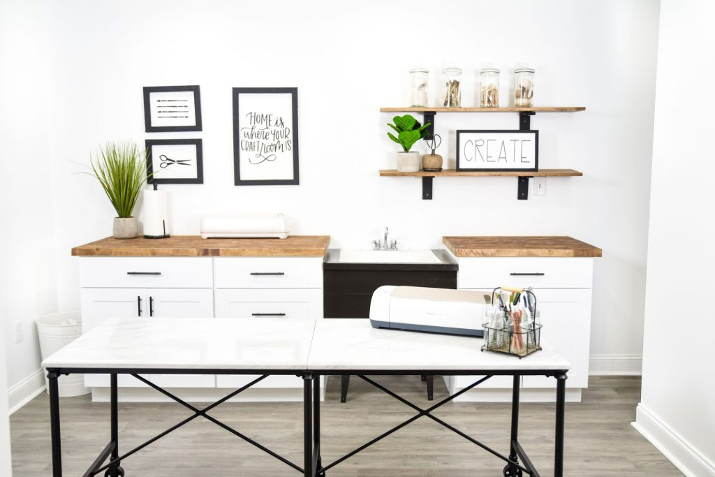 setting up a craft room with a utility sink, cabinets, and open shelving