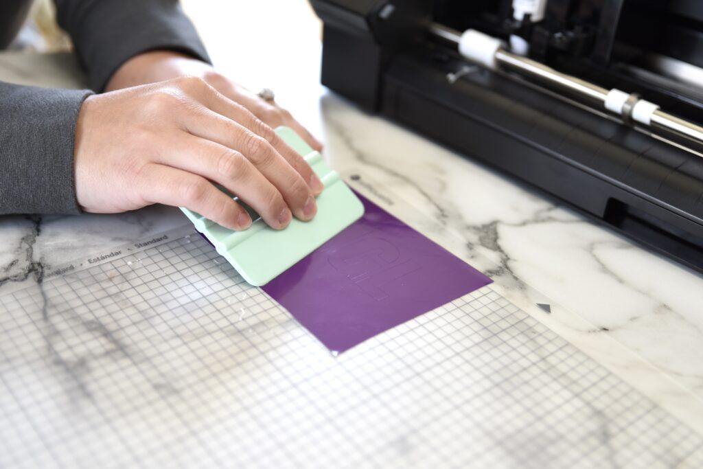 using the scraper tool to burnish vinyl to the mat