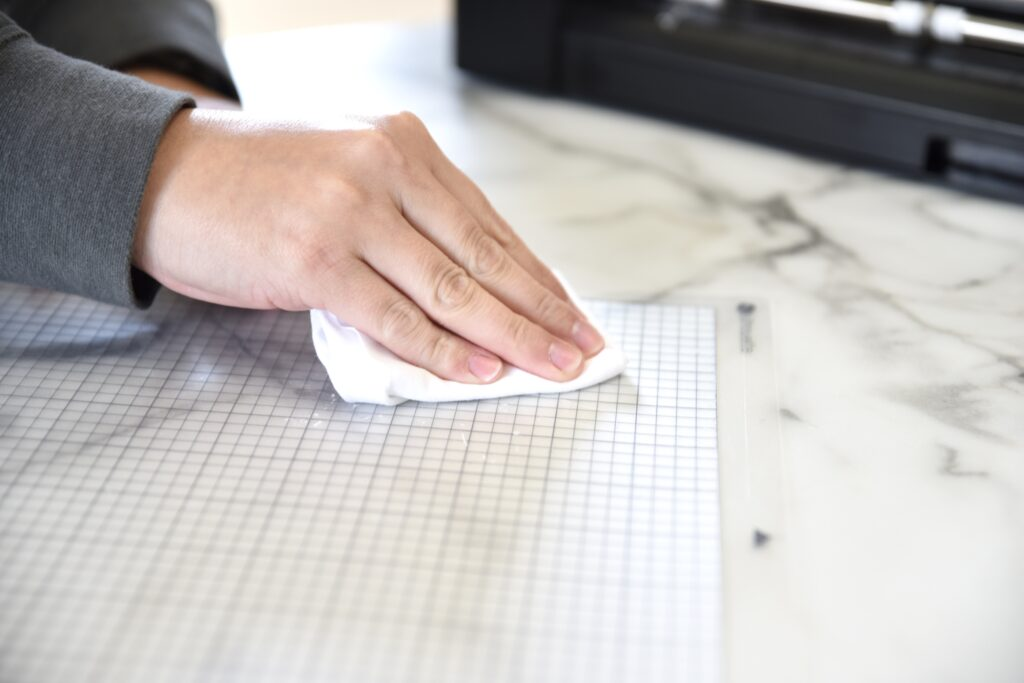 dabbing a silhouette cutting mat with a piece of cotton to reduce stickiness