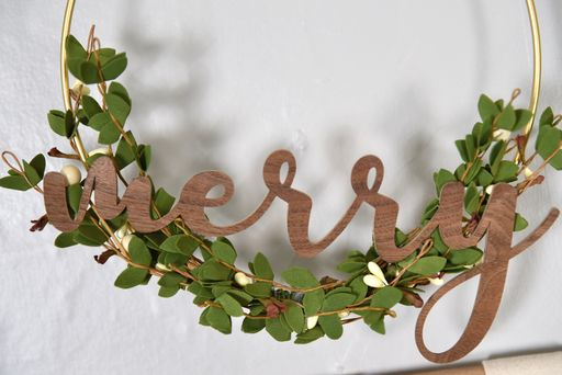 scandinavian christmas mantel closeup of wreath with greenery and word Merry
