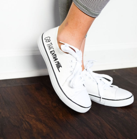 """White tennis shoes with text on the side """"Go the Extra Mile"""" perfect for Spring."""