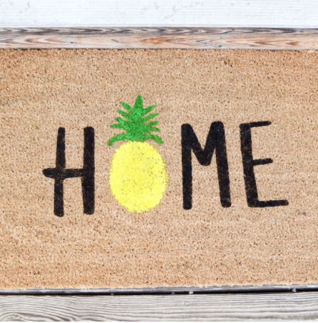 Doormat made with freezer paper technique. Says HOME with a pineapple in place of the O