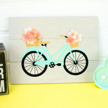 Wooden sign with vinyl die cut of spring colored bicycle, basket on front and back holding flowers