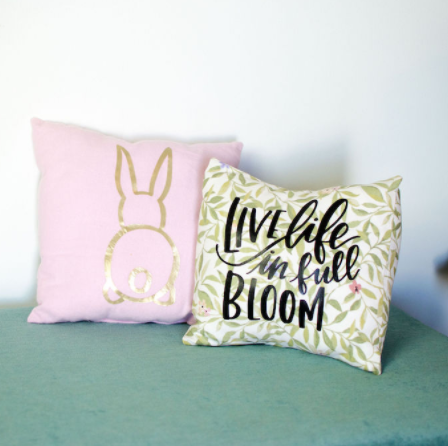 Gold bunny on a pink pillow and another pillow with a word Live Life in Full Bloom