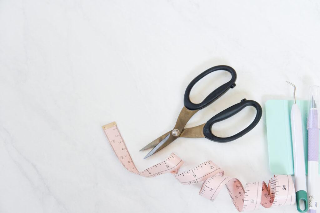 Cricut craft tools including scissors, measuring tape, scraper, weeding tool