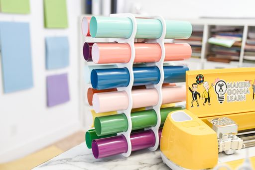 rolls of vinyl in a rack behind a Cricut machine