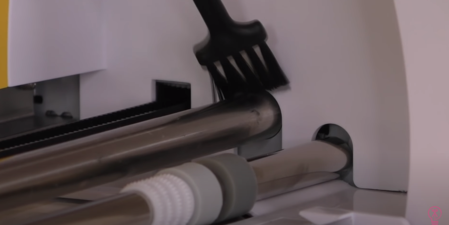 Using A Brush To Clean Debris From Back Rod In Cricut
