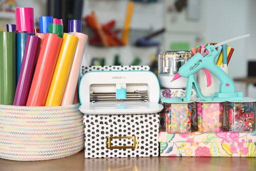 cricut joy machine with vinyl, glue gun, and other craft supplies