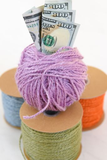 rolls of twine with ball of yarn on top and money sticking out of the top