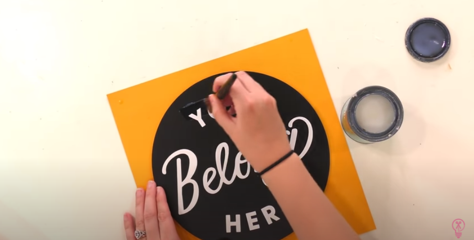 Applying Sealant With Soft Brush Over Sign